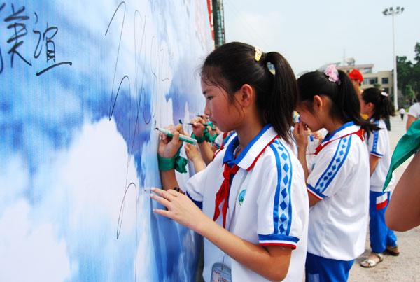 小学生开展了以环保为主题的百米长卷绘画,宣传节能减排,为龙高清图片